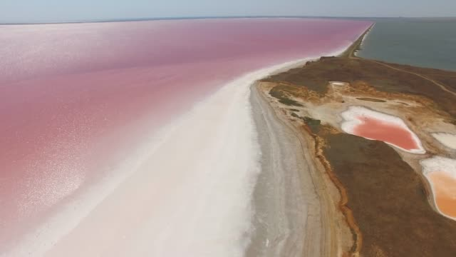 aerial: glittering water surface of red salt lake - salt flat stock videos & royalty-free footage