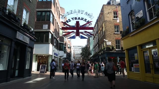 A glittery Union Jack flag sign hangs above Carnaby Street in central London UK on Monday Sept 8 Shoppers walk past stores on Carnaby Street Close...