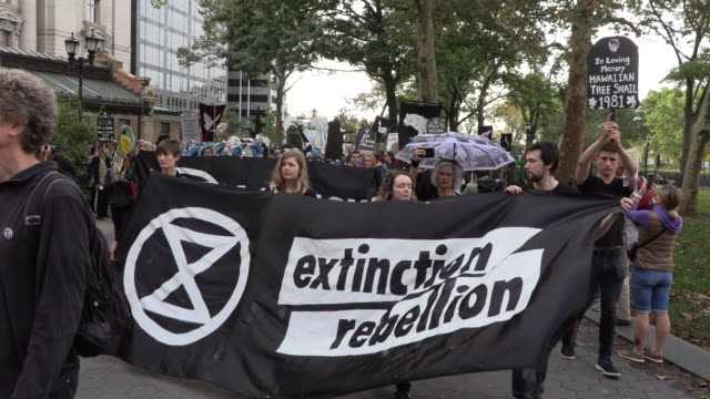 global climate activists extinction rebellion in climate crisis actions shutting down the wall street bull covered in fake blood and a die in at the... - climate finance stock videos & royalty-free footage