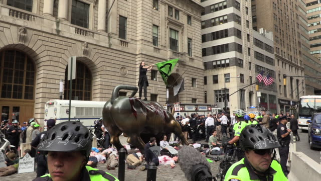 global climate activists extinction rebellion in climate crisis actions shutting down the wall street bull covered in fake blood and a die in at the... - campaigner stock videos & royalty-free footage