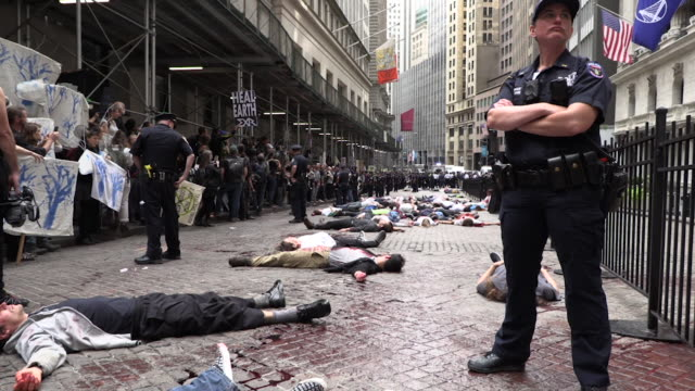 global climate activists extinction rebellion in climate crisis actions shutting down the wall street bull covered in fake blood and a die in at the... - environmental damage stock videos & royalty-free footage