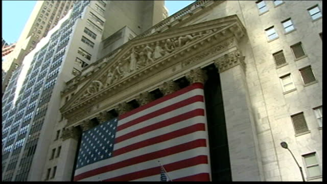 house of representatives approves financial bailout bill us flag outside entrance to new york stock exchange and sign for wall street - 緊急援助点の映像素材/bロール