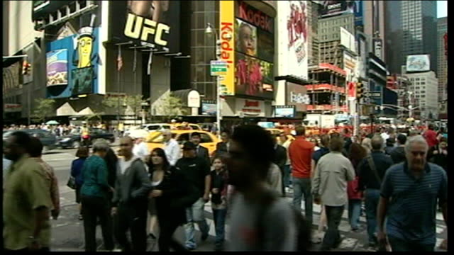 House of Representatives approves financial bailout bill Times Square EXT People along past advertising hoardings people and traffic along on busy...