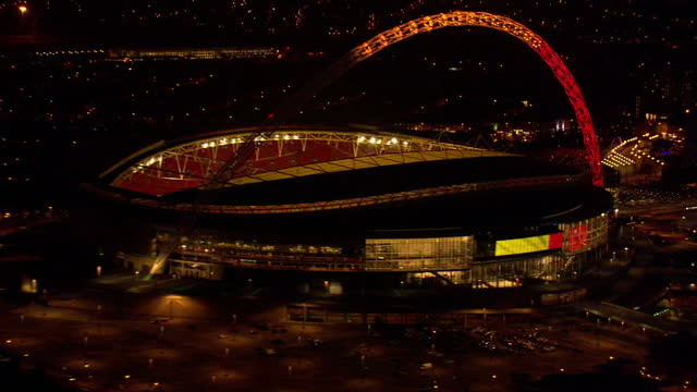global support as belgium mourns victims of twin terror attacks showing aerial nigh shots wembley stadium lit up in belgian flag colours on march 23... - wembley stock-videos und b-roll-filmmaterial