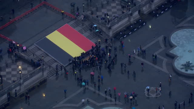 Global Support As Belgium Mourns Victims of Twin Terror Attacks Showing Aerial shots Trafalgar Square showing the large Belgian flag draped across...