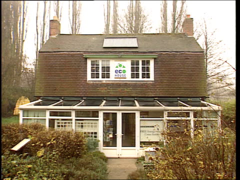 stockvideo's en b-roll-footage met leicester gv eco showhouse zoom in past sign eco house to solar panels on roof chruch farm grammar school pupils listening to talk on energy saving... - vermindering