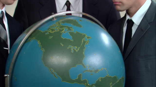 stockvideo's en b-roll-footage met cu globe/ zo ms portrait three businessmen posed around globe looking up at camera then back down at globe/ new york city - bureauglobe