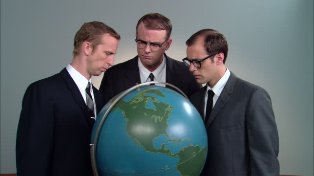 stockvideo's en b-roll-footage met cu globe/ zo ms portrait three businessmen posed around globe looking up at camera with confused faces/ zi globe/ new york city - verwarring