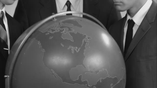 B/W CU Globe/ ZO MS Portrait three businessmen posed around globe looking up at camera then back down at globe/ New York City
