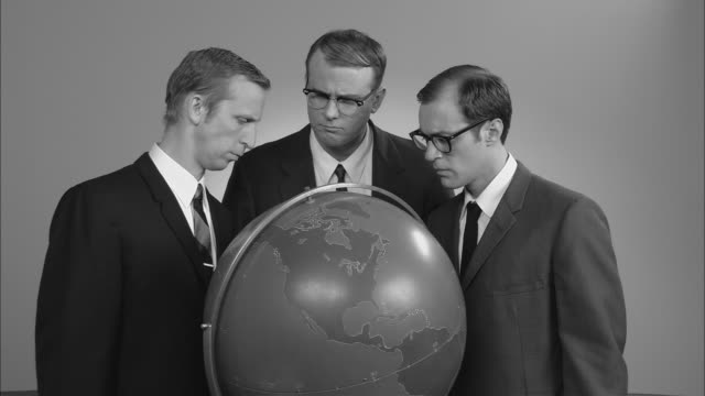 vídeos de stock, filmes e b-roll de b/w cu globe/ zo ms portrait three businessmen posed around globe looking up at camera with confused faces/ zi globe/ new york city - traje completo