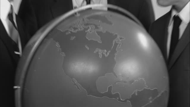 vídeos y material grabado en eventos de stock de b/w cu globe/ zo ms portrait three businessmen posed around globe looking up at camera with surprised faces/ new york city - globo terráqueo para escritorio