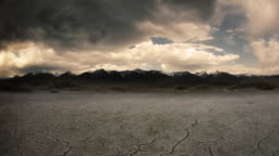 Gloomy dry cracked lake bed in front of mountain