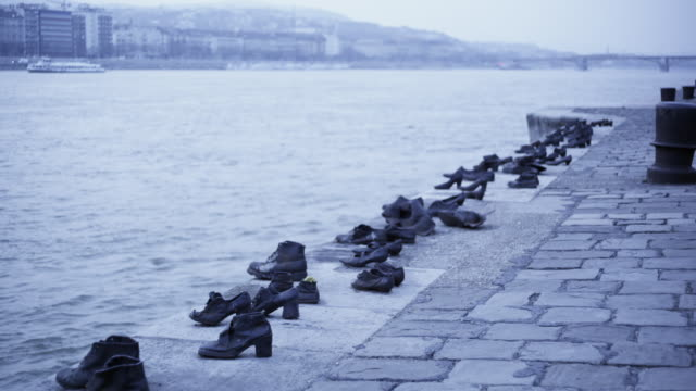 vidéos et rushes de gloomy exterior day shot. the shoes on the danube. memorial of iron shoes representing jewish victoms of the arrow cross militiamen between 1944 and 1945.  promenade on the bank of the danube river in budapest. close up on shoes - budapest