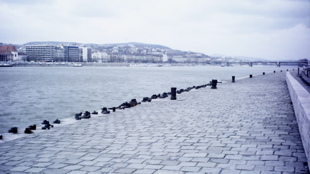 vídeos de stock e filmes b-roll de gloomy exterior day shot. the shoes on the danube. memorial of iron shoes representing jewish victoms of the arrow cross militiamen between 1944 and 1945.  promenade on the bank of the danube river in budapest.  - 1944