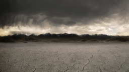 Gloomy storm, cracked lake bed in front of mountain  background.