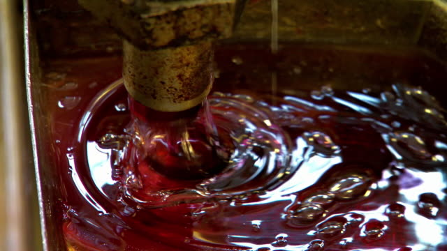 gloopy red syrup pours through machinery - tilt down stock videos & royalty-free footage