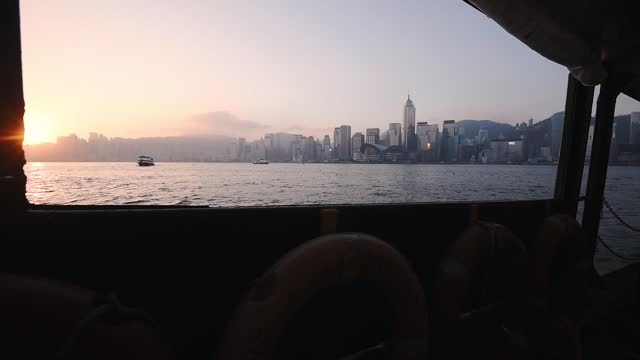 vidéos et rushes de glorious sunset scenery by the victoria harbour while cruising in a ferry boat with hong kong skyline view - wide shot - aller tranquillement