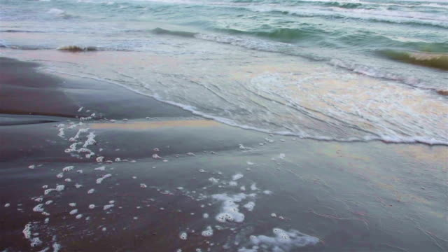 Glossy sand soaks up the sea water as waves crash on the Texas Beach on Padre Island