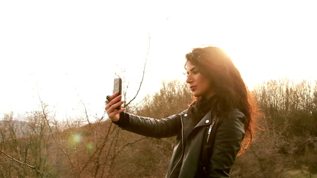 glourious looking brunette is taking a picture of herself with her cellphone - vanity stock videos & royalty-free footage