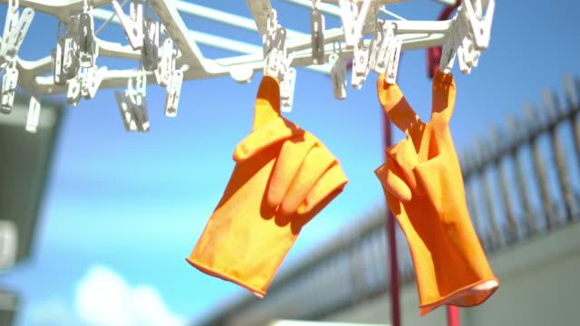 vídeos de stock, filmes e b-roll de forma de luva v signo e polegares para cima pendurados no clipe sobre a luz do sol - arranjo