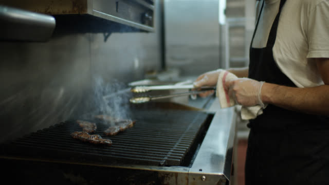 gloved and masked chef grilling meat during covid-19 outbreak - service stock videos & royalty-free footage