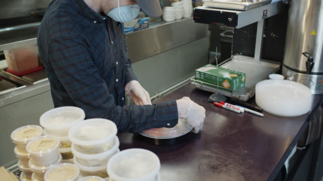 gloved and masked restaurant owner boxing up food for delivery during covid-19 outbreak - fast food stock videos & royalty-free footage