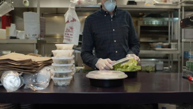 vídeos de stock e filmes b-roll de gloved and masked restaurant owner boxing up food for take out during covid-19 outbreak - edifício de restauração