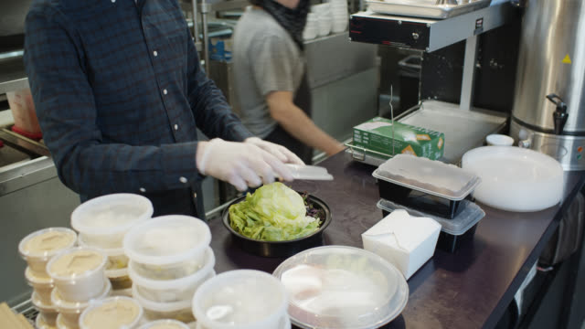 gloved and masked restaurant owner boxing up meal for delivery during covid-19 outbreak - hygiene stock videos & royalty-free footage