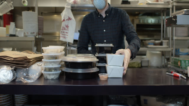 Gloved and Masked Restaurant Owner Boxing Up Meal for Take Out During Covid-19 Outbreak