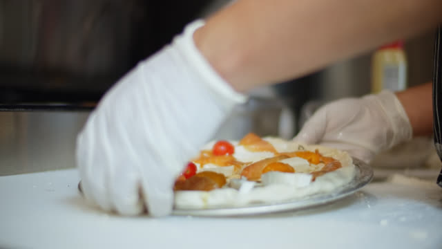 Gloved Chef Spreading Smoked Salmon on Pizza