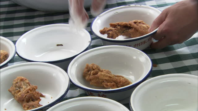 vídeos de stock, filmes e b-roll de gloved female hand placing one piece of fried chicken leg into individual bowls on table - toalha de mesa