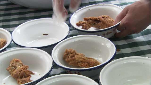 gloved female hand placing one piece of fried chicken leg into individual bowls on table - bordsduk bildbanksvideor och videomaterial från bakom kulisserna