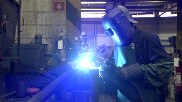 gloved finger adjusts welding; african american male welder jerks head forward causing helmet to slide down over face; side angle, welder's mask... - welding helmet stock videos & royalty-free footage