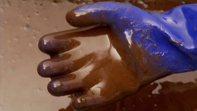 cu ha gloved hand dipping into puddle of crude oil / atlanta, georgia - oil spill stock videos & royalty-free footage