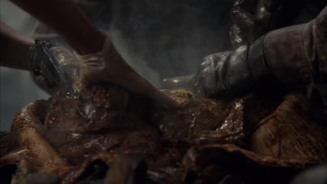 vídeos y material grabado en eventos de stock de a gloved hand gouges into the flesh of an alien with a knife as smoke rises from the body. - limoso