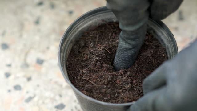 vídeos de stock, filmes e b-roll de mão enluvada fazendo buraco em vaso de flores sujo - buraco