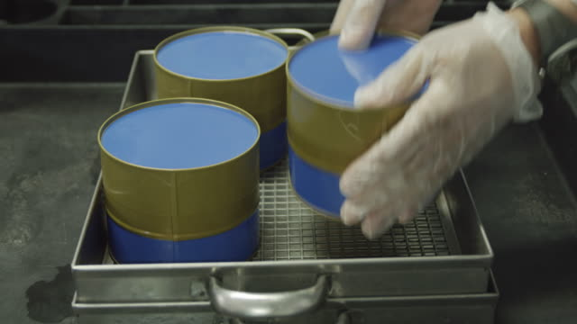 ECU gloved hand of worker affixing label on freshly filled caviar tins to seal them, RED R3D 4K,4KMSTR