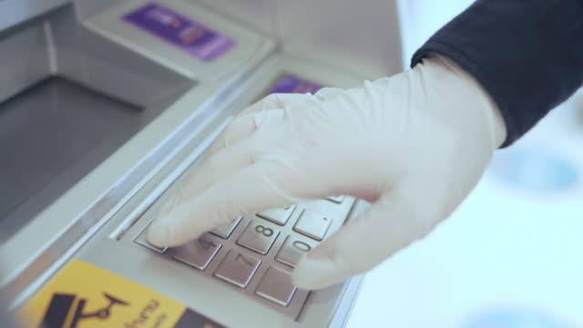 手袋をはめた手は、お金を引き出すためにatmでボタンを押します。コロナウイルス大流行期の保護と安全性の概念, covid-19 - 衛生管理点の映像素材/bロール