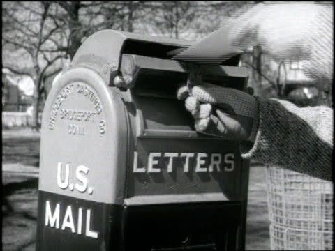 a gloved hand puts a letter in a mail box - letterbox stock videos & royalty-free footage