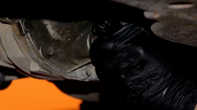 behandschuhte hand ehrerbietig und schmutziges öl ausgießen ablassschraube entfernen - drainage stock-videos und b-roll-filmmaterial