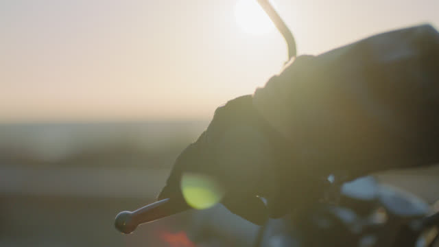cu slo mo. gloved hand twists throttle grip and revs engine on motorcycle overlooking the ocean at sunset. - motorrad stock-videos und b-roll-filmmaterial