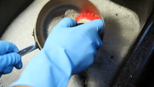 gloved hands and brush scrubbing aluminum pan - washing up stock videos and b-roll footage