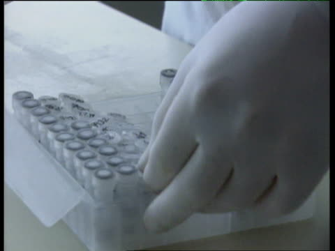 gloved hands of lab technician handling dna samples - camice da medico video stock e b–roll