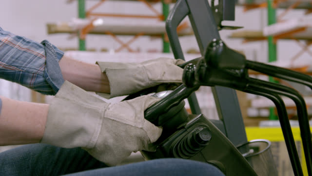 CU gloved hands of man turning forklift steering wheel