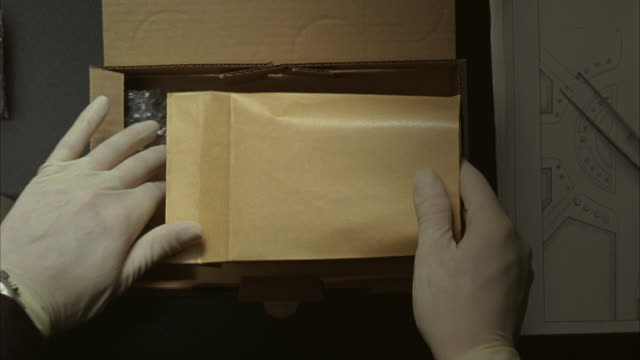 Gloved hands placing a manila envelope filled with Euros and blueprints into a box.