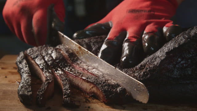 gloved hands slowly cutting perfectly cooked texas barbecue style beef brisket on a rustic cutting board - contestant stock videos & royalty-free footage
