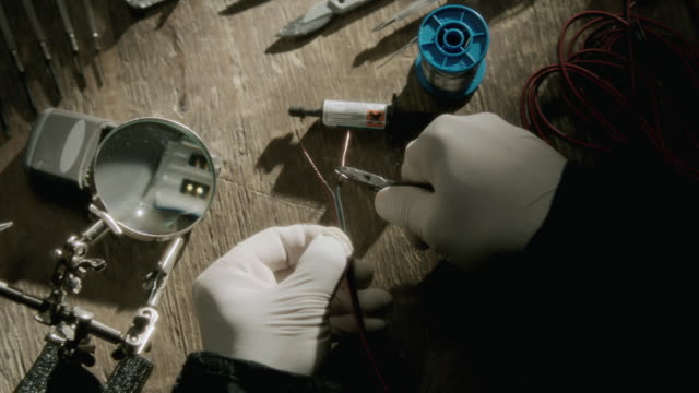 MS Gloved hands stripping thin wires
