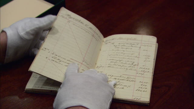 gloved hands turn the pages of an old account book at the tabasco factory. - anatomy stock videos & royalty-free footage