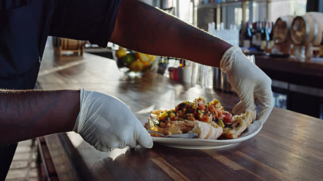 Gloved Server Placing Ceviche on Table