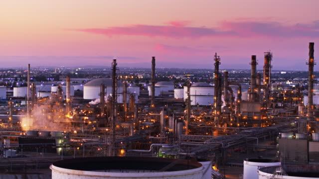vídeos de stock e filmes b-roll de glowing clouds of steam billowing over oil refinery at sunset - aerial shot - wilmington cidade de los angeles